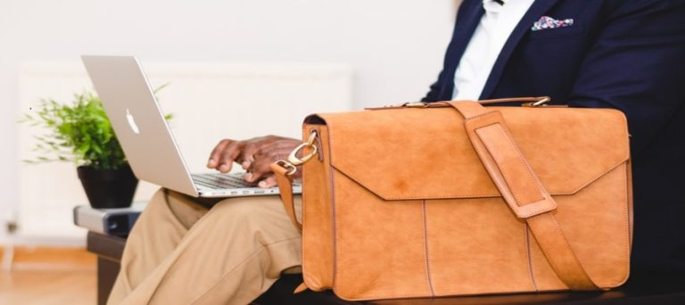 Business man uses laptop and briefcase
